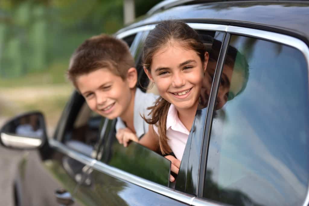 Cheerful kids looking by car window