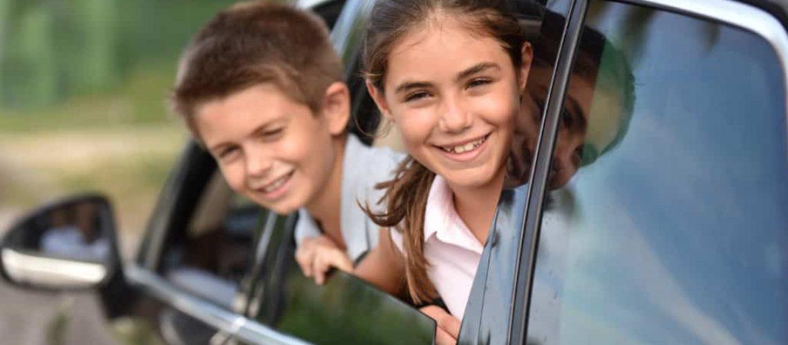 Cheerful kids looking by car window